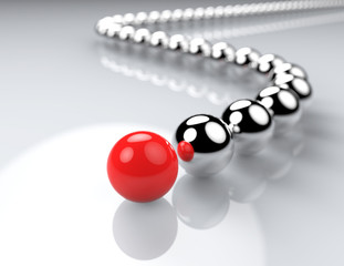 Red ball ahead of metal balls