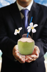 Businessman offer coconut drink at beside beach, Drinks business