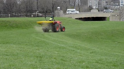 A tractor spreads seed across a grassy lawn in a busy city