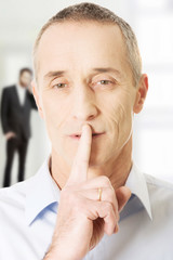 Mature man with finger on lips.