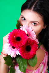Spring portrait of a pretty young brunette with a bunch of gerbe