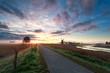 beautiful sunrise on dutch farmland with windmill