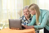 Senior woman with her caregiver in home using laptop.