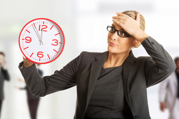 Businesswoman holding a big clock