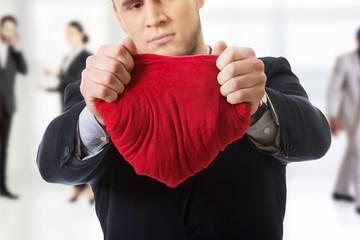 Businessman tears heart shaped pillow.