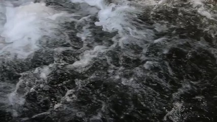 Water moves quickly in a wave before it plunges into a waterfall