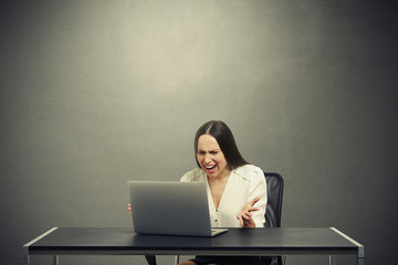 angry businesswoman looking at laptop