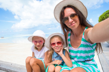 Mother and little girls taking selfie at tropical beach