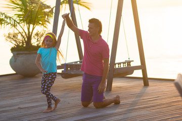 Happy father and his adorable little daughter relax at evening