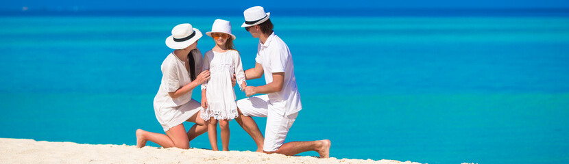 Young family of three on white beach during summer vacation