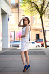 Beautiful young girl in white dress walking summer street