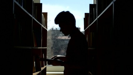 Silhouette of  young student reading a book in a library