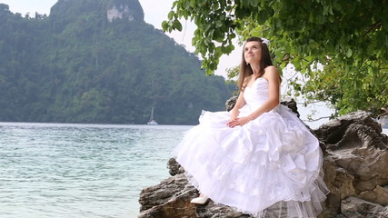 brunette beautiful bride sits on rock smiles