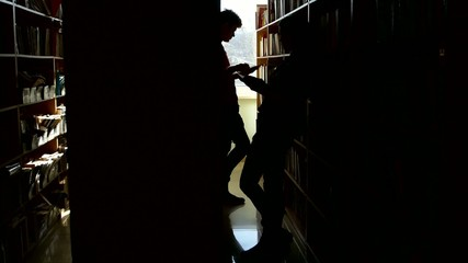 Silhouette college student talk between the bookshelves in a