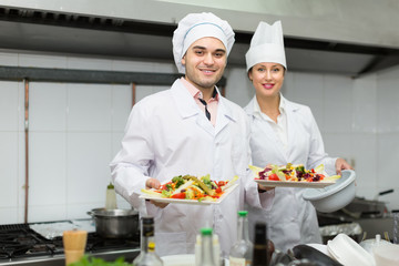 Two cooks at restaurant kitchen