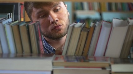 Young man browsing through the racks of books in a library