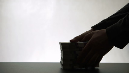 Silhouette of person takes pile paper money to another person