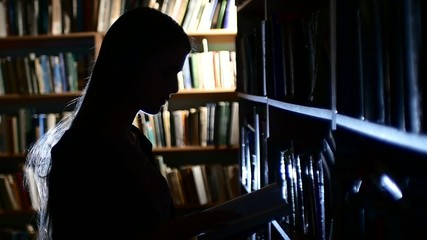 pretty young college student in a library, chooses a book. Close