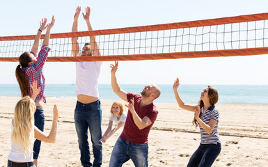 People play volleyball on beach