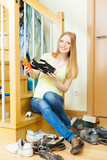 Smiling long-haired woman cleaning shoes