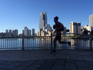 Silhouette of man running to work in city