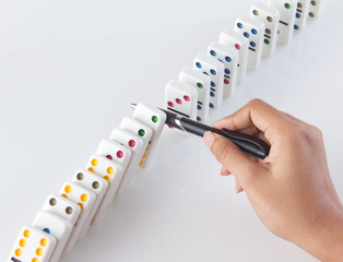 Person stopping falling dominoes with a pen