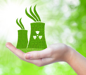 Nuclear power plant icon in hand on green natural background.