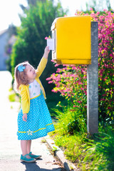 Little girl with an envelope next to a mail box