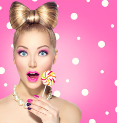 Funny girl eating lollipop over pink polka dots background
