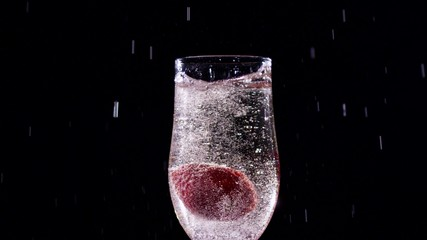 Strawberry splash in a champagne flute. Slow motion. Close up.