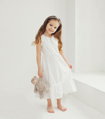 Cute little girl with teddy bear at home in white room