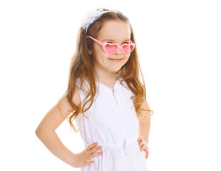 Fashion kid. Beautiful little girl in the pink sunglasses on a w