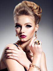 Pretty girl with beautiful hairstyle  and gold jewelry, bright m
