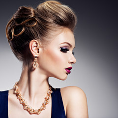 Beautiful woman with style hairstyle  and gold jewelry with brig