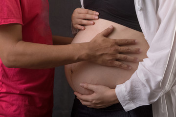 Pregnant woman and her husband touch belly, isolated