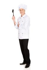 Chef holding black plastic spoon