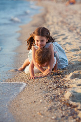 Two cute little siblings playing on the beach