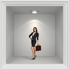 Young girl with leather briefcase standing in window lights on