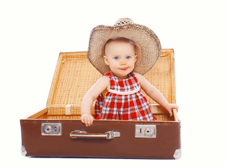 Funny kid in a summer hat is sitting on a suitcase