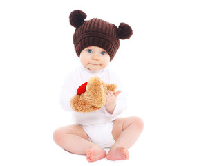 Sweet baby in brown hat sitting with toy