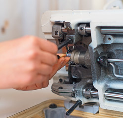 Female hand fixing sewing machine. Maintenance.