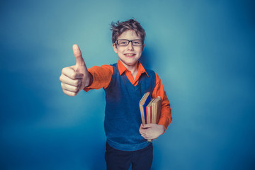 European-looking  boy of ten years in glasses showing thumb up,