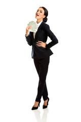 Full length businesswoman holding polish bills