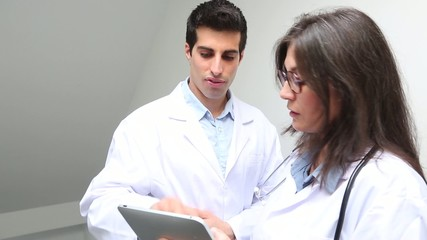 Male and female doctor talking and using tablet computer