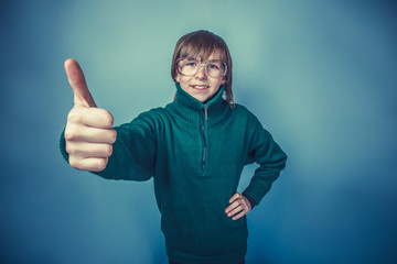 European -looking boy of ten years showing thumbs up on blue bac