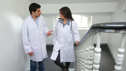 Two doctors, a man and a woman, discuss going up the stairs