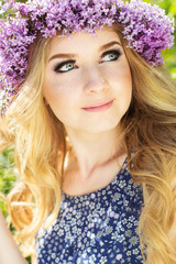 Teen blonde girl with wreath from lilac flowers