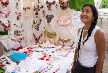 Hispanic woman admiring embroidered  Mexican blouses