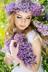 Blue-eyed blonde girl with wreath from lilac flowers