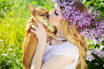 Beautiful girl with lilac flowers is kissing chuhuahua dog